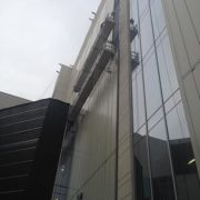 side view of glass building with scaffold