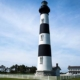 The Bodie Island Lighthouse standing tall against the blue sky.
